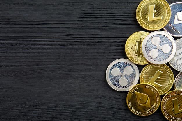 Srebrne i złote monety z symbolem bitcoin, ripple i ethereum na tle drewna.