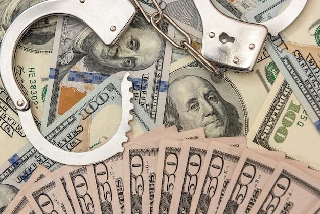 Srebrne kajdanki leżące na dolarach amerykańskich, pojęcie przestępczości