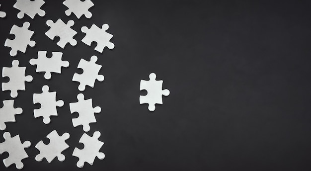 Srebrne metalowe puzzle na czarnym kolorze