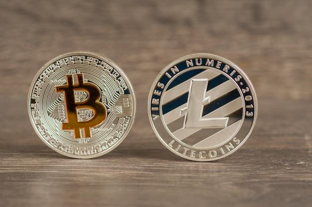 Srebrne monety bitcoin i litecoin na drewnianym stole