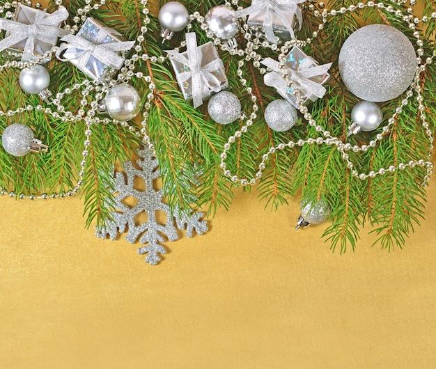 Srebrne ozdoby świąteczne na świerkowej gałęzi na złotym tle