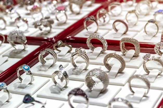 Srebrne pierścionki z diamentami i innymi kamieniami szlachetnymi na wystawie jubilerskiej.