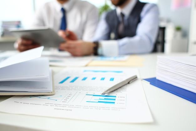 Srebrne pióro leży na ważnym papierze przy stole z grupą kolegów