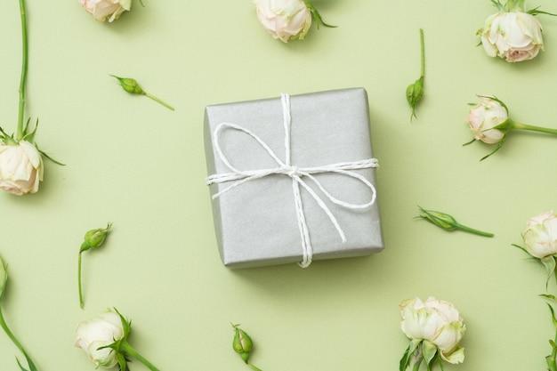 Srebrne pudełko upominkowe. białe róże na zielonym stole. widok z góry.