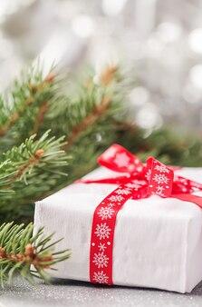 Srebrne świąteczne nieostre światła bokeh z gałęzi jodły i pudełkiem prezentowym