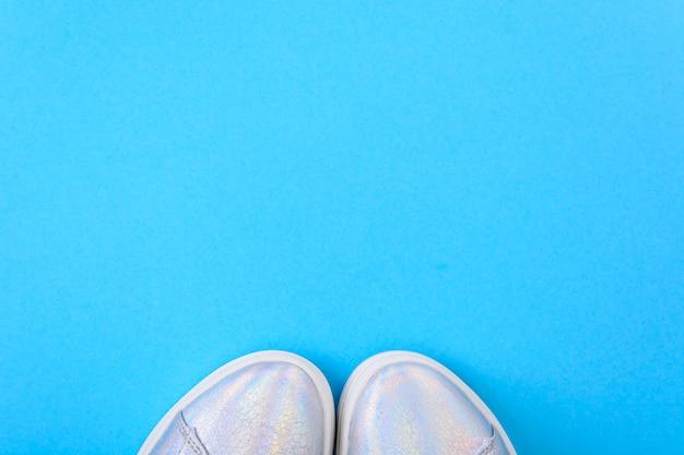 Srebrne trampki na niebieskiej powierzchni