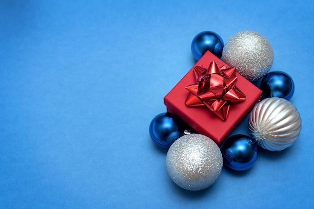 Srebrno-niebieskie bombki i czerwone pudełko z prezentem