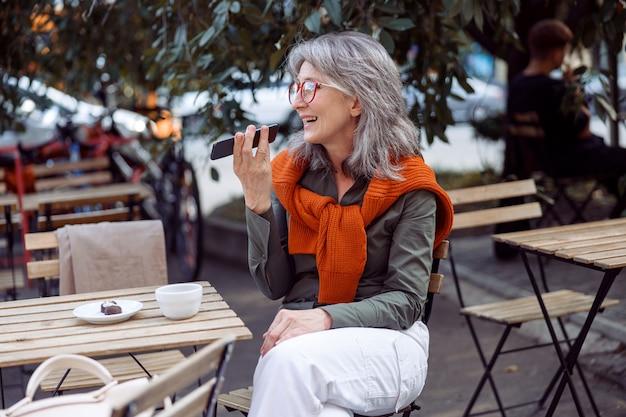 Srebrnowłosa dama w okularach używa trybu głośnika w telefonie na tarasie kawiarni na świeżym powietrzu