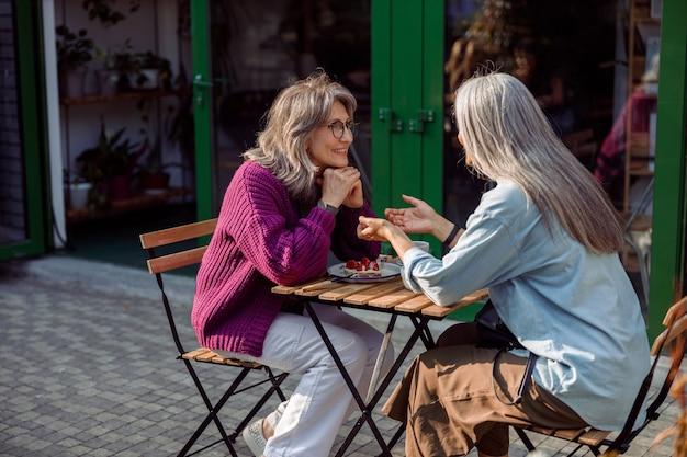 Srebrnowłosa kobieta opowiada historię dojrzałej przyjaciółce siedzącej przy stole na świeżym powietrzu