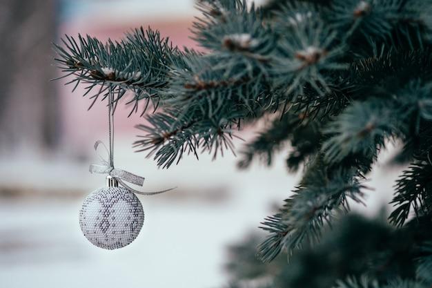 Srebrny biały christmas ball na gałęzi jodły z bliska