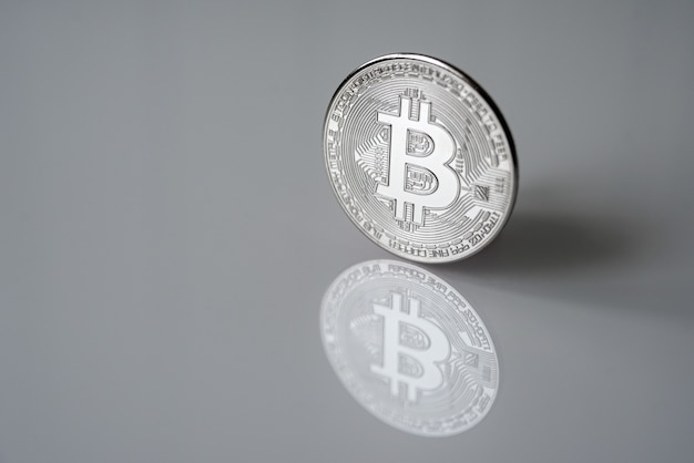 Srebrny bitcoin (btc) na odblaskowej powierzchni