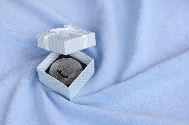 Srebrny bitcoin leży w małym niebieskim pudełku z małym łukiem