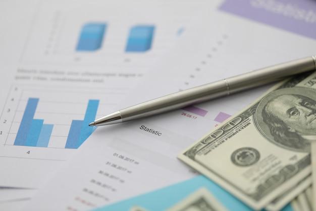 Srebrny długopis leży na gotówce dolara z biznesem