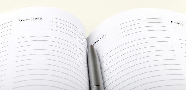 Srebrny długopis na porządku obrad otwartego biznesu na białym tle