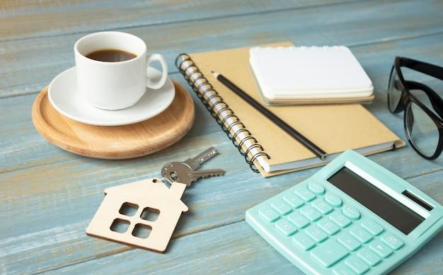 Srebrny klucz do domu leżący na drewnianym stole, leasing, ubezpieczenie lub hipoteka w koncepcji nieruchomości, oglądany pod niskim kątem z naciskiem na końcówkę.