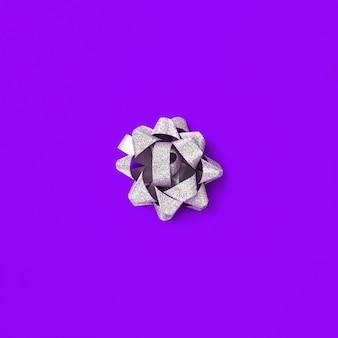 Srebrny łuk na fioletowym tle papieru. błyszcząca kokardka ze wstążki. protonowy fiolet.
