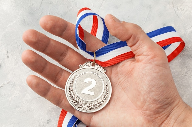 Srebrny medal. nagroda za drugie miejsce ze wstążką, którą mężczyzna trzyma w dłoni.