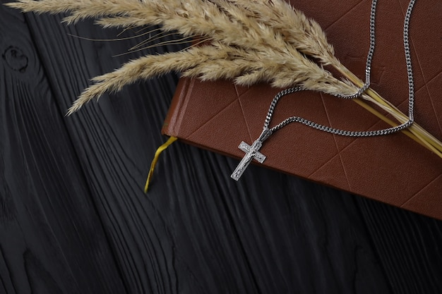 Srebrny naszyjnik, krzyż krucyfiks i gałąź pszenicy na chrześcijańskiej księdze świętej biblii na czarnym drewnianym stole, widok z góry