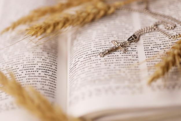 Srebrny naszyjnik z krzyżem krucyfiksem na chrześcijańskiej księdze świętej biblii na czarnym drewnianym stole