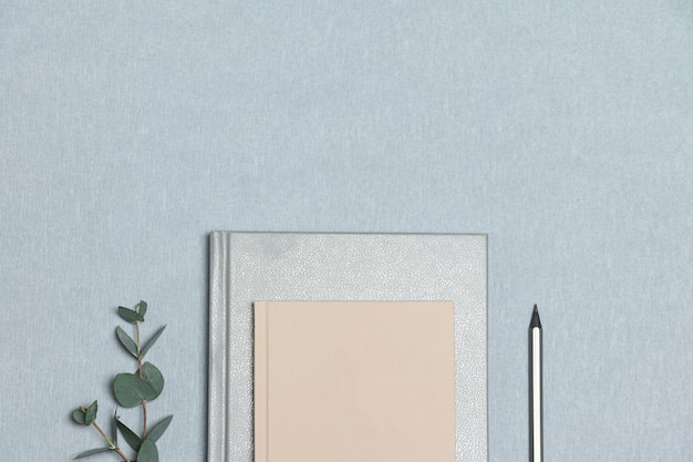 Srebrny notatnik i ołówek, różowa notatka, zielona roślina na szarym tle