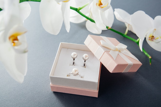 Srebrny pierścionek i kolczyki z perłami w ozdobnym pudełku z białym kwiatem orchidei. prezent na wakacje. akcesoria modowe