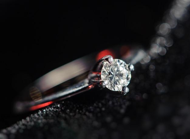 Srebrny pierścionek na czarnym tle. obraz makro