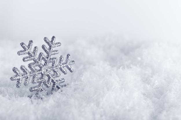 Srebrny płatek śniegu na tle puszystego śniegu przeznaczone do walki radioelektronicznej zima symbol z dekoracyjną zabawką