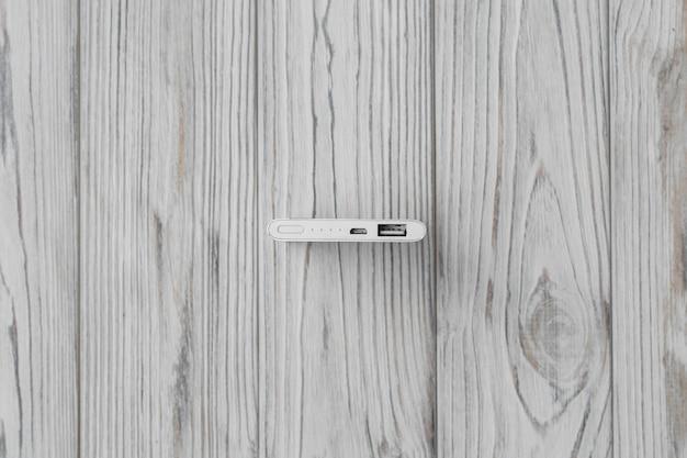 Srebrny powerbank z usb na drewnie