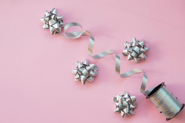 Srebrny prezent łuk na białym tle na różowym tle. ozdobne kokardki. papier do pakowania. prezenty, obchody walentynek, niespodzianka urodzinowa.