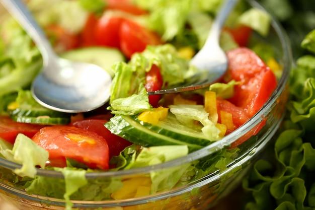 Srebrny widelec i łyżka w talerzu mieszają sałatki ze świeżych warzyw doprawionych oliwą z oliwek. surowe jedzenie i wegetarianizm w nowoczesnym społeczeństwie jest popularnym pojęciem.