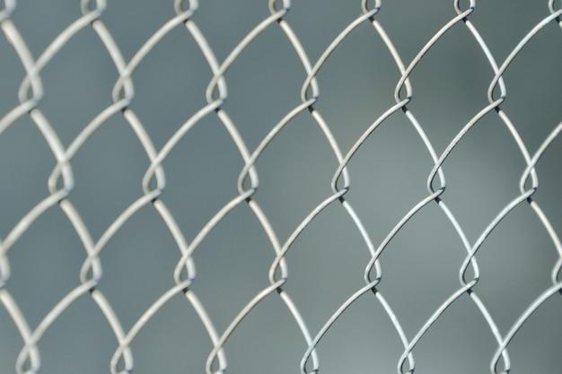 Srebrzyste ogrodzenie wykonane z metalowej siatki płyty, na szarej, rozmytej przestrzeni. zbliżenie
