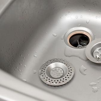 Srebrzysty zlew kuchenny z rozmontowanym filtrem ochronnym podczas procesu naprawy