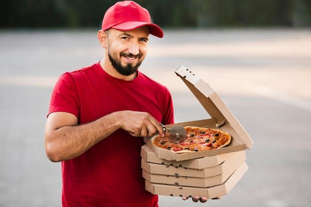 Średni facet dostawy pizzy krojenie pizzy
