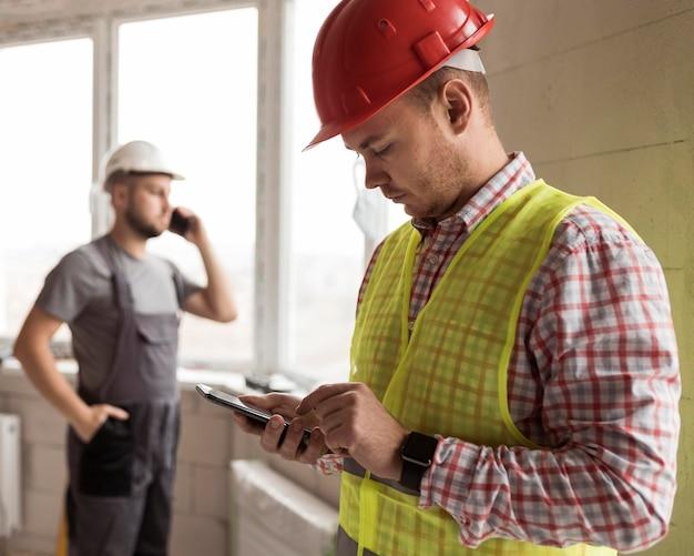 Średni mężczyźni budowniczy ze smartfonami