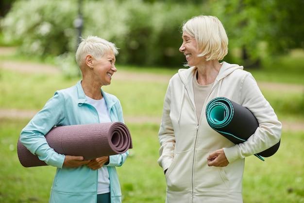 Średni portret dwóch wesołych koleżanek w strojach sportowych trzymających maty do jogi, spędzających razem czas w parku