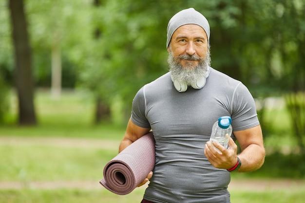 Średni portret przystojny brodaty starszy mężczyzna trzyma matę do jogi i butelkę wody stojącej w parku patrząc na kamery