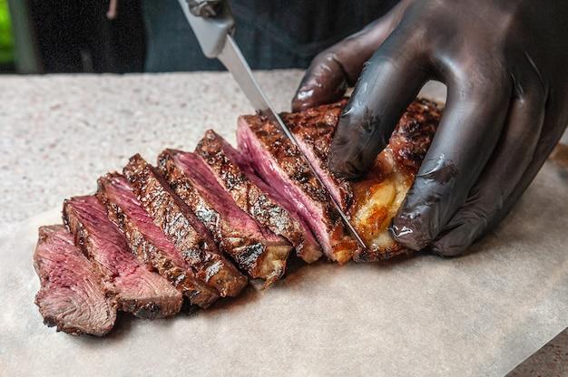 Średni stek z pieczonej wołowiny. pokrój nożem na kawałki. męskiej dłoni w czarnej rękawiczce. stek leży na pergaminie. zbliżenie.