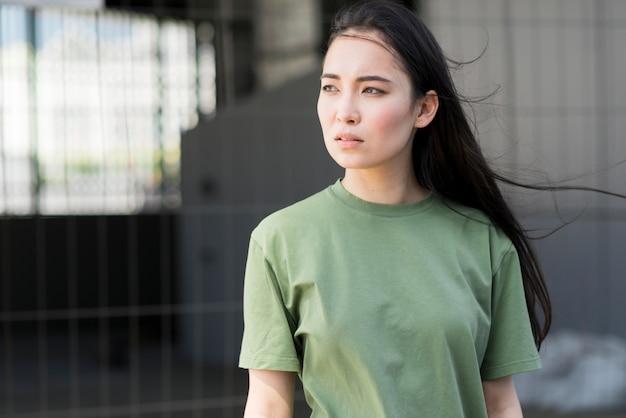 Średni strzał azjatykcia kobieta patrzeje daleko od