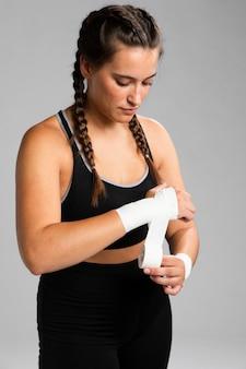 Średni strzał bandażujący jej ręki widok z przodu kobiety