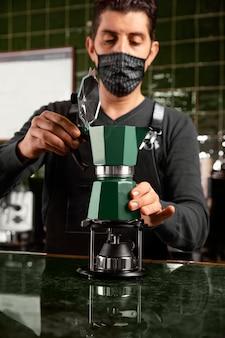 Średni strzał barista z maską przygotowujący kawę