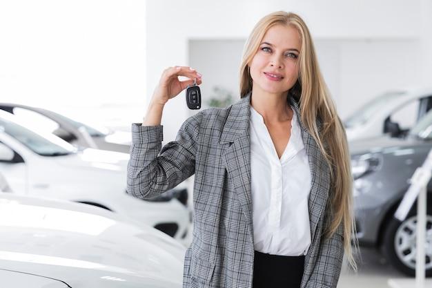 Średni strzał blondynki kobieta trzyma samochodowego klucz