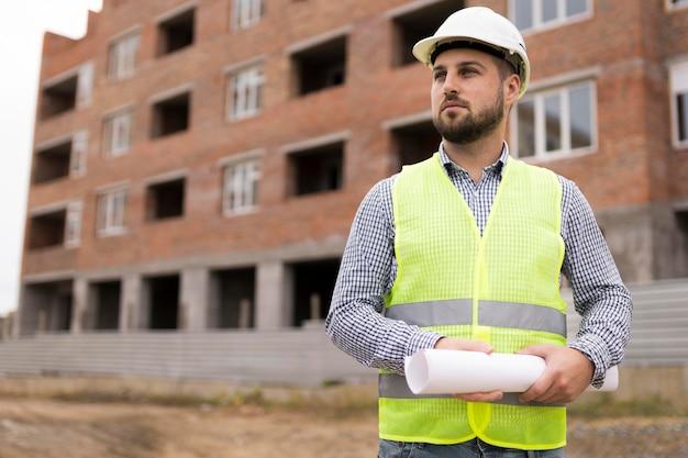 Średni strzał budowniczy mężczyzna trzyma projekt