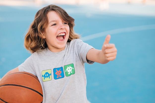 Średni strzał chłopca z koszykówką