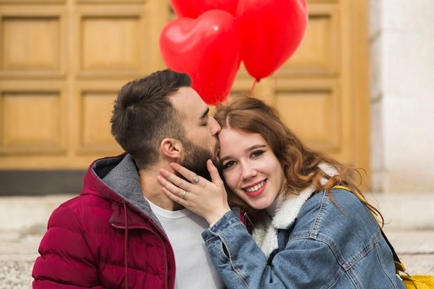 Średni strzał człowieka całuje dziewczynę