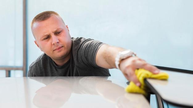 Średni strzał człowieka czyszczącego samochód szmatką