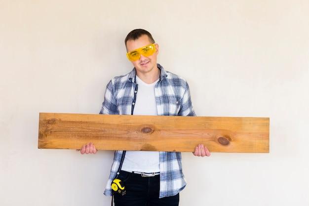 Średni strzał człowieka posiadającego kawałek drewna