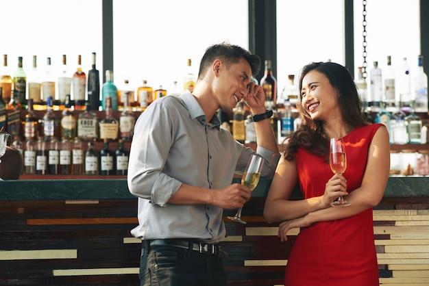 Średni strzał dwóch nieznajomych flirtujących w barze pijących szampana