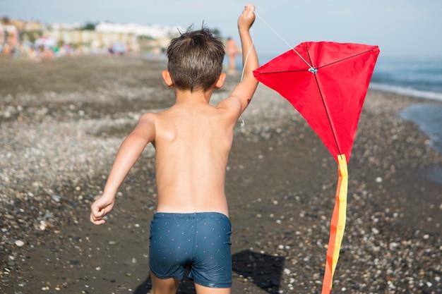 Średni strzał dzieciak bawiący się latawcem