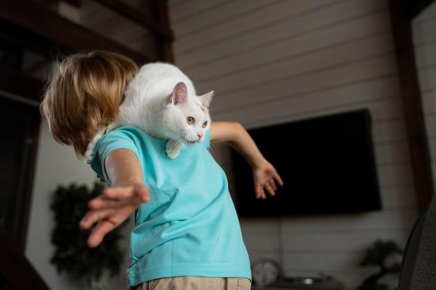 Średni strzał dzieciak bawiący się z kotem