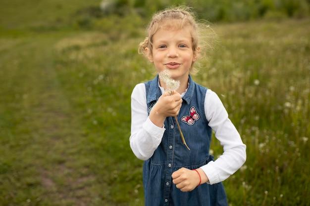 Średni strzał dzieciak trzymający mniszek lekarski